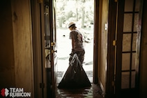 A volunteer with Team Rubicon collects debris from a resident's home in Beaumont, Texas. Many of the homes damaged by Hurricane Harvey had major reconstruction due to mold and water damage. Volunteers from all over the country, including a group of seven Airmen assigned to Whiteman Air Force Base, Mo., traveled south to the affected region to provide aid.