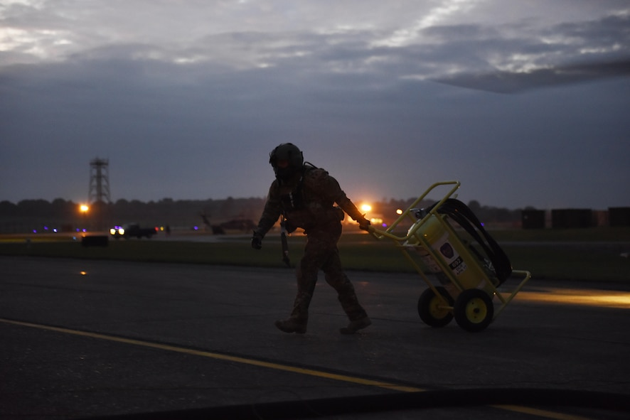 A staff sergeant who is an HH-60G Pave Hawk crewman from the 56th Rescue Squadron moves a fire extinguisher away from the helicopter taxi area at Royal Air Force Lakenheath, England, Oct. 26. The Pave Hawk helicopters are refueled while running to minimize time on the ground. (U.S. Air Force photo/ Airman 1st Class John A. Crawford)