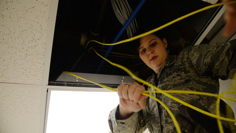 Senior Airman Margaret Merkling, 819th RED HORSE Squadron knowledge operator, pulls communication wires from a ceiling Oct. 31, 2017, at Malmstrom Air Force Base, Mont.