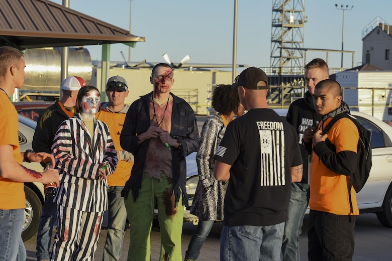 Volunteers stand by and receive a brief about their roles for the haunted house event during Ghoulfellow at Louis F. Garland Department of Defense Fire Academy on Goodfellow Air Force Base, Texas, Oct. 28, 2017. The fire training tower was a prop for the haunted house and was just one of the activities that took place during Ghoulfellow. (U.S. Air Force photo by Airman 1st Class Zachary Chapman/Released)