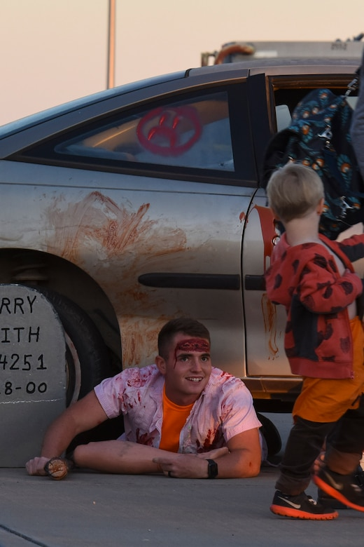 A volunteer dressed as a zombie scares a child as they leave the haunted house of Ghoulfellow at Louis F. Garland Department of Defense Fire Academy on Goodfellow Air Force Base, Texas, Oct. 28, 2017. One part of the event was the haunted house set up in the fire training tower and showcased jump scares, smoke machines and dark walk ways. (U.S. Air Force photo by Airman 1st Class Zachary Chapman/Released)