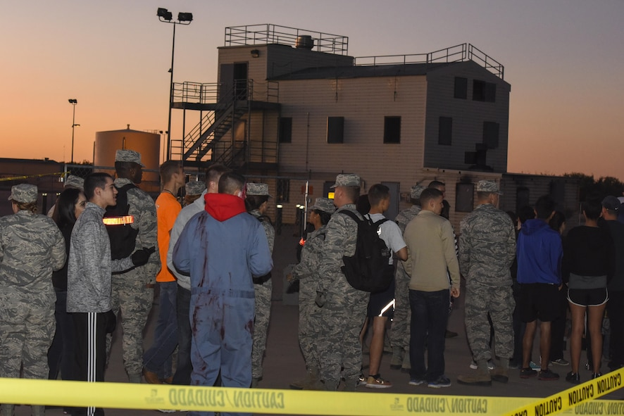 Guests wait in line to enter the haunted house at Louis F. Garland Department of Defense Fire Academy on Goodfellow Air Force Base, Texas, Oct. 28, 2017. The haunted house was just one activity of Ghoulfellow and was located at the fire training tower. (U.S. Air Force photo by Airman 1st Class Zachary Chapman/Released)
