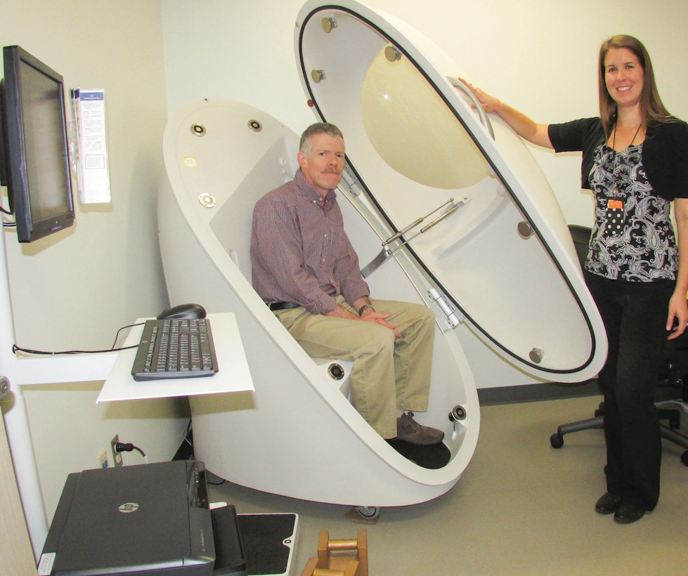 Guy Leahy and Kirsten David of the Health Promotions Flight show off the new Bod Pod at the 377th Medical Group building. The machine measures percentage of body fat and has several features the older Bod Pod didn't.