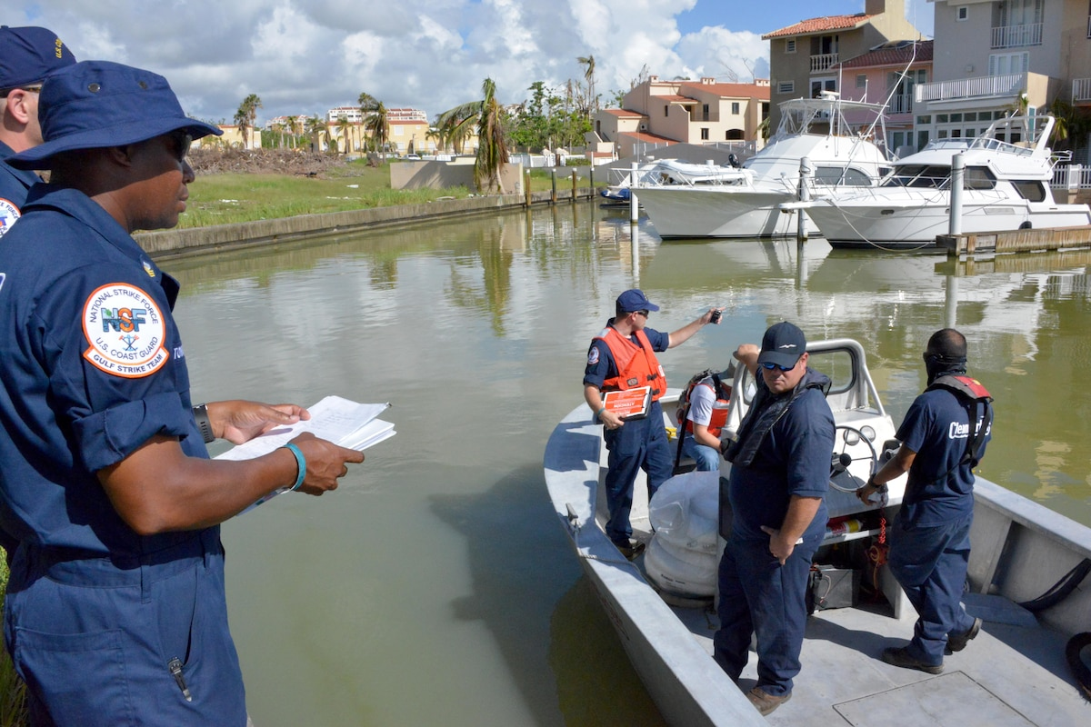Members of the Coast Guard on land and on a boat talk.