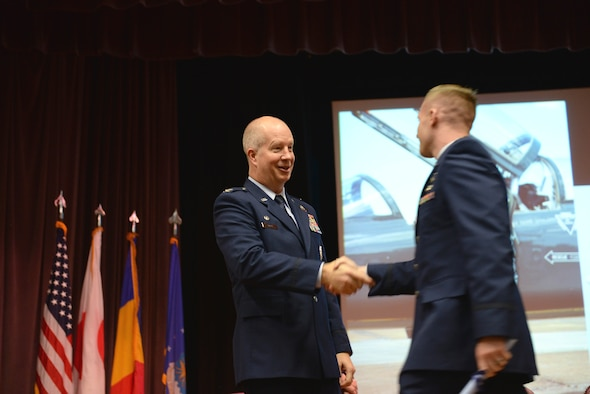 Col. Joel Carey, 12th Flying Training Wing Commander, shakes the hand of 2nd Lt. Emerson Cameron, Specialized Undergraduate Pilot Training Class 18-01 pilot, Oct. 27, 2017, on Columbus Air Force Base, Mississippi. Carey spoke in front of the class to commemorate the graduates and give them words of encouragement for the hard work ahead of them. (U.S. Air Force photo by Airman 1st Class Keith Holcomb)