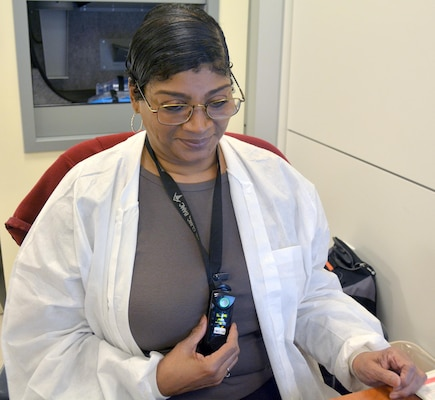 Gina Brown uses the wireless hands-free integrated communications system, or WHIICS, to contact another staff member Nov. 1. The Brooke Army Medical Center Information Management Division implemented the WHICS last October, but the system was fully employed Oct. 5 to allow alarms from patient monitors to automatically contact the appropriate personnel through the device.