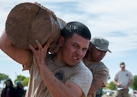 "Airman 1st Class Dalton Cruz, 377th Weapons Systems Security Squadron, carries a log with his teammate during the ""Team Punisher"" portion of the Manzano Challenge at Kirtland Air Force Base, N.M., Oct. 27, 2017. The challenge required more than 70 volunteers and coordination with 21 base agencies to make the event a success. (U.S. Air Force photo by Staff Sgt. J.D. Strong II)"