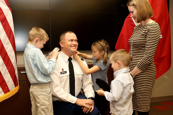 Maj. Christopher Burkhart, U.S. Army Corps of Engineers Nashville District deputy commander, enjoys the moment as his wife and children put on his new rank of lieutenant colonel during a promotion ceremony in Nashville, Tenn., Nov. 2, 2017. (USACE photo by Mark Abernathy)