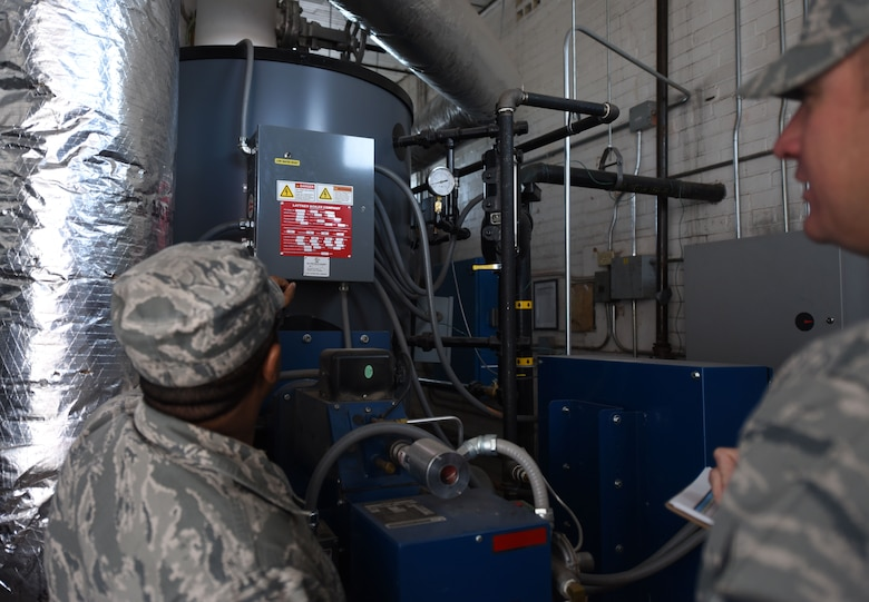 Tech. Sgt. Grahame Evelyn, 90th Civil Engineering Squadron heating ventilation air conditioning technician, gives Tech. Sgt. Charles Hernandez data to write in the log, on F.E. Warren Air Force Base Wyo., Oct. 31 2017. The data is used to track trends to find root causes that are affecting large systems such as hard water or corrosion in old pipes, causing HVAC systems to fail. (U.S. Air Force Photo by Airman 1st Class Braydon Williams)