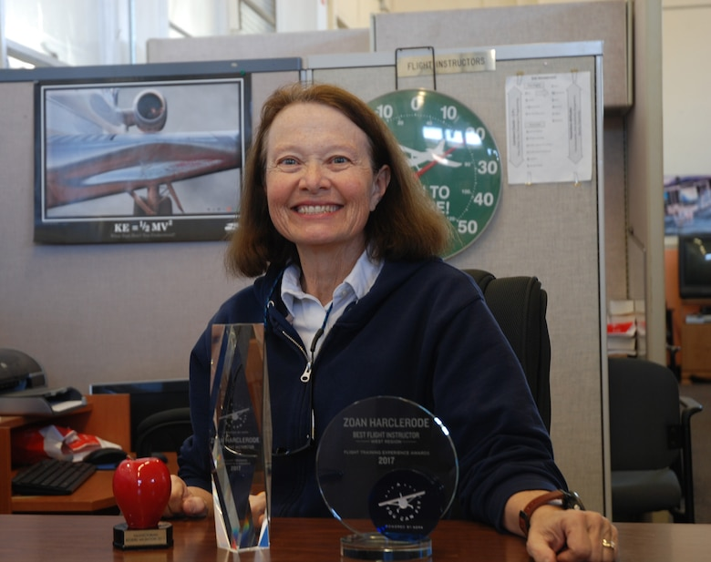 Zoan Harclerode, flight instructor at the Rocky Mountain Flight Training Center on Peterson Air Force Base, Colorado, poses at her desk with her Westeren Region and National Pilot of the Year awards Oct. 31, 2017. The Aircraft Owners and Pilots Association recognized her from among 2,012 nominated pilots.  (U.S. Air Force photo by Dave Smith)
