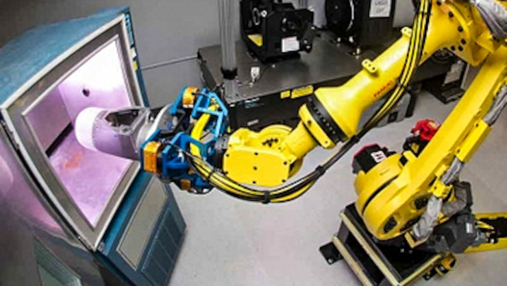 A yellow robotic arm extends inside an oven.
