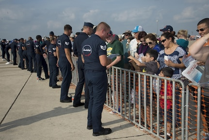 """Members of the U.S. Air Force Aerial Demonstration Squadron """"Thunderbirds"""" team sign autographs during the 2017 Joint Base San Antonio Air Show and Open House Nov. 4, at JBSA-Lackland, Kelly Field Annex.  Air shows allow the Air Force to display the capabilities of our aircraft to the American taxpayer through aerial demonstrations and static displays.  The air show gives attendees an opportunity to get up close and personal to see some of the equipment and aircraft used by the U.S. military today. (U.S. Air Force photo by Melissa Peterson/Released)"""