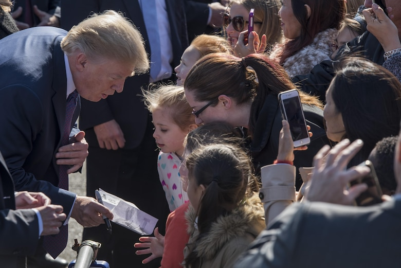 President Donald J. Trump signs a note from a young audience member, Nov. 5, 2017, at Yokota Air Base, Japan.