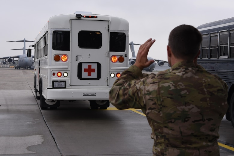 A volunteer for the En-route Patient Staging program helps guide a medical bus on the flightline on Ramstein Air Base, Germany, Oct. 26, 2017. Patients remain on the bus until accommodations on the plane are ideal for travel.