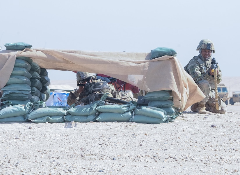 Two soldiers crouch behind a structure.