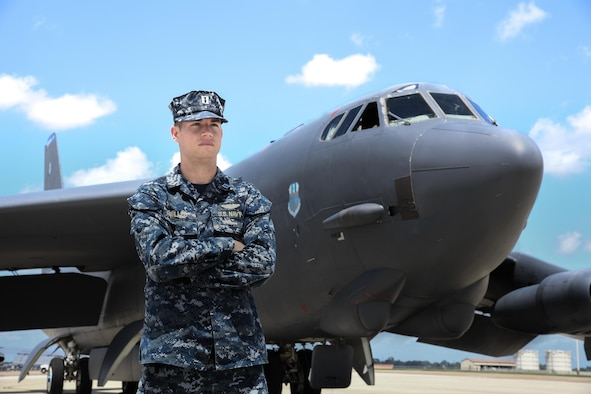 U.S. Navy Lt. Andrew Willes stands in front of a B-52 on a flightline at Barksdale AFB, Louisiana.
