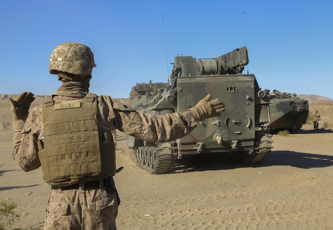 Staff Sgt. Austin Kulas, 3rd Assault Amphibious Battalion, guides the Amphibious Assault Vehicle during a field test to load a Mine Clearing Line Charge in a Mark-154 Mod 1 Launcher at Range 114 aboard the Marine Corps Air Ground Combat Center, Twentynine Palms, Calif., Oct. 26, 2017. Unlike current amphibious breaching systems, the MICLIC will allow a breach lane that provides maneuverability for assault forces as they push forward to provide fire and maneuver on enemy defended beaches that are manned with explosives. (U.S. Marine Corps photo by Cpl. Christian Lopez)