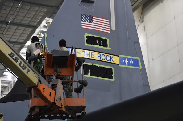 Airman paint new tail flash to tail of C-130.