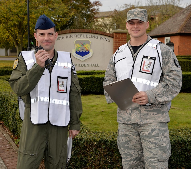 "U.S. Air Force Master Sgt. Robert King and U.S. Air Force Tech. Sgt. Nicolas Bevilacqua, 100th Air Refueling Wing Inspector General inspection and exercise planners, show off their ""white cell"" vests as they pose for a photo Nov. 3, 2017, on RAF Mildenhall, England. The IG members wear white vests and wing inspection team members wear red vests to show their non-player status as they evaluate each scenario to ensure it is played out correctly. RAF Mildenhall members should treat the exercise scenario as though the evaluators are not there, and respond accordingly to the situation. (U.S. Air Force photo by Karen Abeyasekere)"