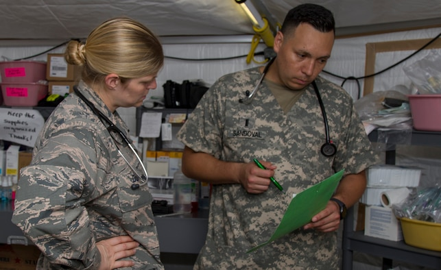 AGUADILLA, Puerto Rico – U.S. Air Force Capt. Jennifer Dunn, with the 331st Emergency Medical Support from Langley Air Force Base, and Army 1st Lt. Benjamin Sandoval, 331st Minimal Care Detachment, 49th Medical Battalion, 332nd Medical Brigade, U.S. Army Reserves, speak with a patient in front of Buen Samaritano Hospital, Nov. 3, 2017. Air Force, Army, and the Minnesota-1 disaster medical assistance team work together to provide medical aid from DMAT tents while the hospital prepares to open. (U.S. Army photo by Sgt. Avery Cunningham)
