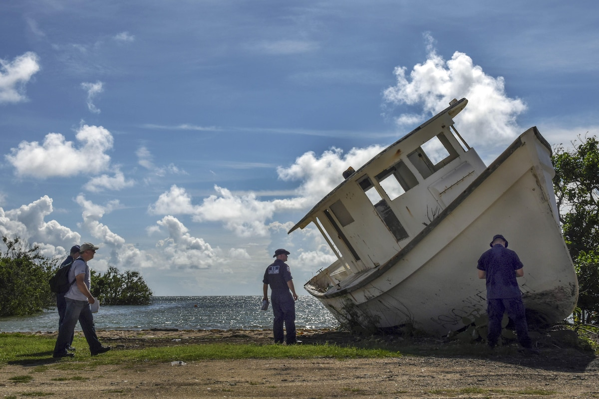 Uniformed personnel examine a muddy boat tipped on its side on a stretch of shore.