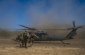 Pararescue airmen carry a patient to a helicopter.