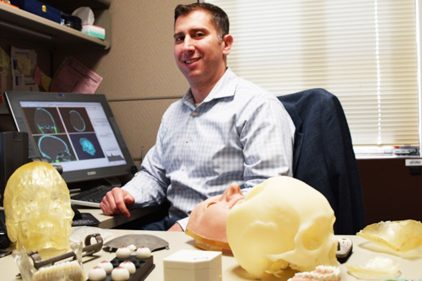 A man sits at a desk with 3-D printed medical applications.