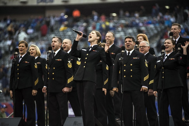 A group of sailors sing on the field at a stadium.