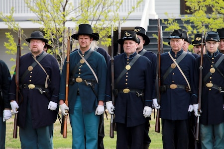 Fort Scott's Civil War reenactors stand at attention in uniforms that resemble the 1800s.