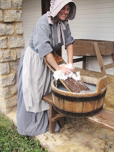A reenactor washes cloth on a washboard. Fort Scott has 20 historical sites throughout the city.