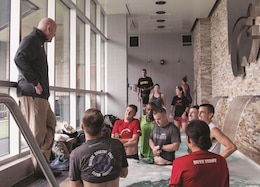 Phillip Vardiman, athletic training program director, Kansas State University, speaks to the 1st Infantry Division Army Ten-Miler team at the Vanier Family Football Complex, K-State, Sept. 26. The team sat in a 65-degree, waist-high pool, a recovery treatment used by the K-State athletes.