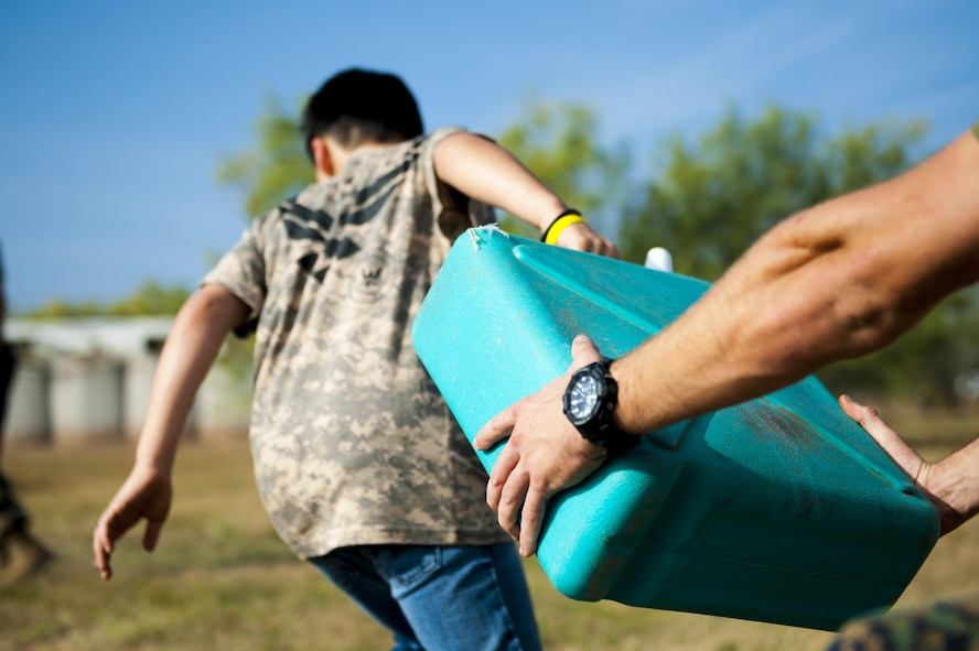 A participant of Operation Kids Investigating Deployment Services picks up a water container before running an obstacle course at the Afghan Village on Goodfellow Air Force Base, Texas, Nov. 4, 2017. During Operation KIDS, volunteer children interacted in simulated deployed environments. (U.S. Air Force photo by Senior Airman Scott Jackson/Released)