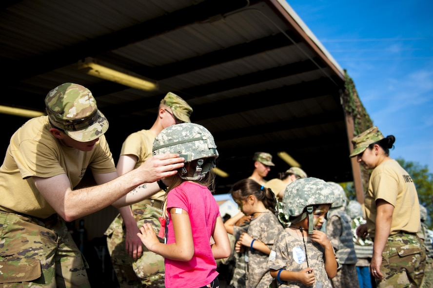 Volunteers assist participants of Operation Kids Investigating Deployment Services don helmets at the Afghan Village of Goodfellow Air Force Base, Texas, Nov. 4, 2017. This was the largest iteration of Operation KIDS with 100 children from the base and local community participating. (U.S. Air Force photo by Senior Airman Scott Jackson/Released)