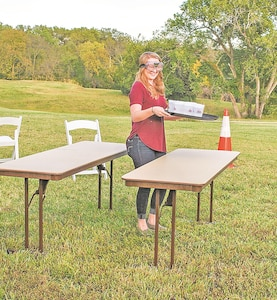 Ashley Church, wife of Pfc. Antianna Church, Medical Department Activity, slips between two tables while wearing goggles that impair her vision on the drunken-waiter obstacle course during Volksfest Sept. 29 at Riley's Conference Center.