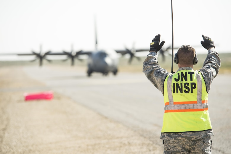 Tech. Sgt. Attila Csipes, 49th Logistics Readiness Squadron Small Air Terminal non commissioned officer in charge, marshals a C-130 Hercules down the runway of White Sands Missile Range's Condron Airfield N.M., for Vigilant Shield 18 on Oct. 31, 2017.  This exercise tests the response and deployment capabilities of Airmen and Soldiers. The aircraft based out of Littlerock AFB, Ark., flew equipment in from Fort Drum, N.Y., to support the 10th Mountain Division Soldiers that will take part in the exercise.  (U.S. Air Force photo by Tech. Sgt. Jeff Howerton)