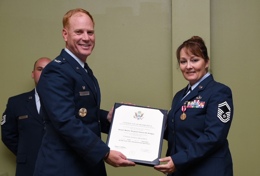 Col. James W. Kellogg, 94th Airlift Wing commander, presents Senior Master Sgt. Donna Bridges, 94th AW law office superintendent, with her certificate of retirement at Dobbins Air Reserve Base, Ga. Nov. 4, 2017. Bridges served 34 years in the U.S. Air Force. (U.S. Air Force photo/Senior Airman Justin Clayvon)