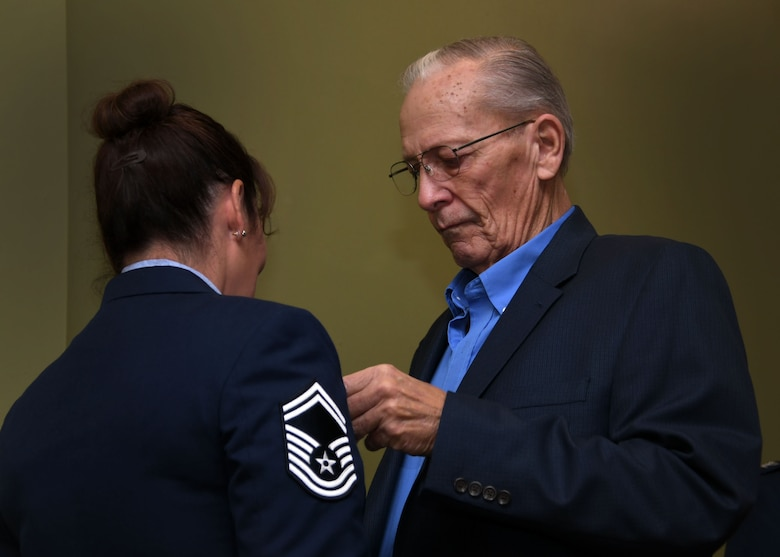 Bob DeLancy pins a retirement medal on Senior Master Sgt. Donna Bridges, 94th Airlift Wing law office superintendent, at Dobbins Air Reserve Base Nov. 4, 2017. Her father played a key role in her joining the military as he signed the necessary paperwork so she could join the U.S. Air Force at age 17. (U.S. Air Force photo/Staff Sgt. Miles Wilson)
