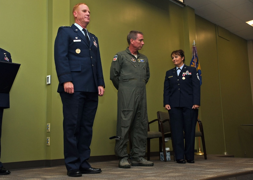 From left, Col. James Kellogg, 94th Airlift Wing commander; Master Sgt. Todd Owens, 700th Airlift Squadron loadmaster; and Senior Master Sgt. Donna Bridges, 94th AW law office superintendent; stand on stage shortly before Kellogg presented Owens with a spouse certificate of appreciation at Bridges' retirement ceremony Nov. 4, 2017. The certificate was presented to Owens, Bridges' husband, to show the wing's appreciation for his support throughout Bridges' 34-year career. (U.S. Air Force photo/Staff Sgt. Miles Wilson)
