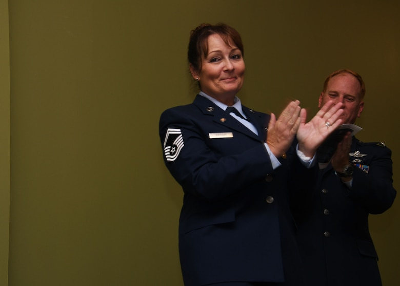 Senior Master Sgt. Donna Bridges, 94th Airlift Wing law office superintendent, claps during her retirement ceremony at Dobbins Air Reserve Base, Ga. Nov. 4, 2017. She retired after 34 years of service, with 27 of those years spent as a paralegal. (U.S. Air Force photo/Staff Sgt. Miles Wilson)