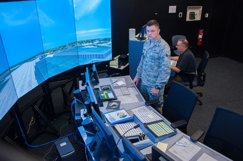Senior Airman Zachary Cinnamon, 88th Operations Support Squadron air traffic controller, runs through an air traffic control scenario on Wright-Patterson's simulator as Jack Wilson, Air Traffic Control Tower Simulator administrator, operates the simulator behind him. The simulator allows controllers to train on complex air traffic control scenarios safely, preparing them to handle real-life operations. (U.S. Air Force photo/John Harrington)