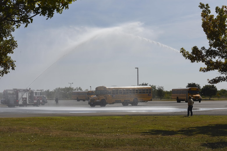 Buses carrying the children participating in Operation Kids Investigating Deployment Service are welcomed home by two streams of water from firetrucks at the Louis F. Garland Department of Defense Fire Academy on Goodfellow Air Force Base, Texas, Nov. 4, 2017. The kids experienced what a deployment may be like when a parent has to deploy. (U.S. Air Force photo by Airman 1st Class Zachary Chapman/Released)
