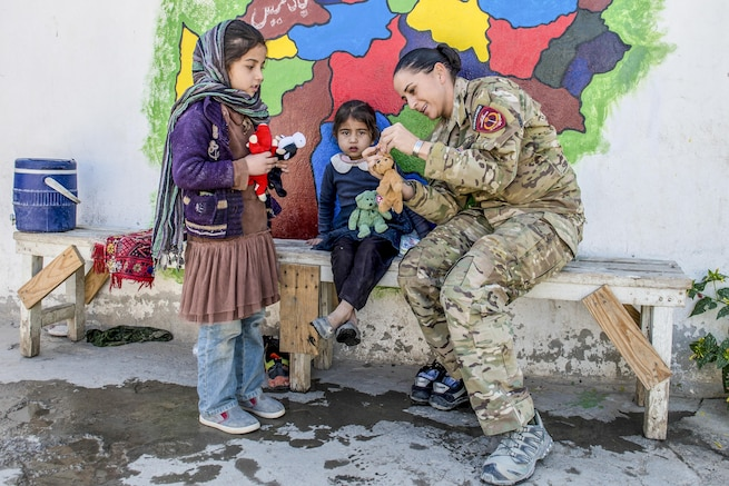 A soldier and two girls handle small stuffed animals while gathered in front of a bright mural.