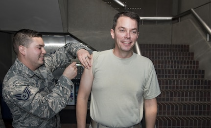 U.S. Air Force Staff Sgt. Jacob Radford, left, 628th Aerospace Medical Squadron allergy and immunizations technician, administers the annual flu shot to U.S. Air Force Col. Jeffrey W. Nelson, right, 628th Air Base Wing commander, during a mobile flu line in the Joint Base Charleston Headquarters Building Nov. 7, 2017.