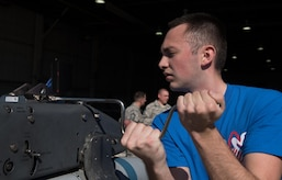 U.S. Air Force Airman 1st Class Nicholas Potter, 94th Aircraft Maintenance Unit load crew member, prepares to load weapons onto a rack during The 3rd Quarter Weapons Load Competition at Joint Base Langley-Eustis, Va., Nov. 3, 2017. Potter was part of a three-man team that raced to complete a successful load of a U.S. Air Force F-22 Raptor, without any infractions. (U.S. Air Force photo by Staff Sgt. Carlin Leslie)