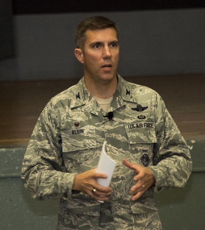 U.S. Air Force Col. John Klein, the commanding officer of the 60th Air Mobility Wing, addresses the audience during an All Call at the Base Theater, Nov. 6, 2017, Travis Air force Base Calif. Klein spoke about leadership, pride and maintaining readiness. (U.S. Air Force photo by Heide Couch)