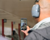 An honorary commander takes a video of a defender from the 60th Security Force Squadron Humvee during their tour of the 60th Mission Support Group, Nov. 3, 2017 at Travis Air Force Bace, Calif. The purpose of the Travis Air Force Base Honorary Commander Program is to promote relationships between base senior leadership and civilian partners, foster civic appreciation of the Air Force mission and its Airmen, maximize opportunities to share the Air Force story with new stewards, and to communicate mutual interest, challenges, and concerns that senior leaders and civilian stakeholders have in common. (U.S. Air Force photo by Louis Briscese)
