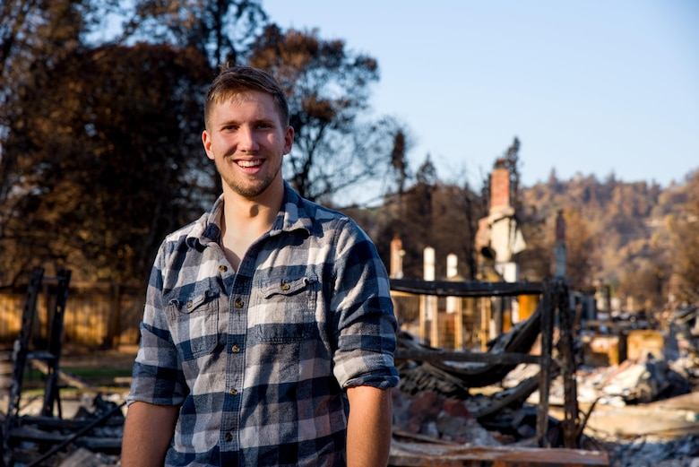 Senior Airman Martin Baglien, 349th Civil Engineer Squadron firefighter, smiles as he tells how lucky he feels that his family survived the California wildfire in Santa Rosa, Calif., on Oct. 31, 2017. Behind Baglien lies what remains of his family's neighborhood after the fire ravaged it.