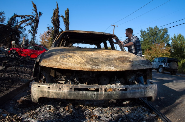 Senior Airman Martin Baglien, 349th Civil Engineer Squadron firefighter, inspects the shell of his father-in-law's car after the California wildfire in Santa Rosa, Calif., on Oct. 31, 2017. Baglien was woken up by his family in the early hours of the morning after the wildfires started.