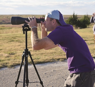 Shawn Stratton, supervisory fish and wildlife biologist for Directorate of Public Works Environmental Division, scans the horizon for elk during the stop of the tour that overlooks the rolling hills at Fort Riley Sept. 30 during the installation tour.