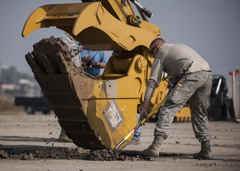 U.S. Air Force Senior Airman Kyle Gibson, 8th Civil Engineer Squadron Water and Fuel Systems Maintenance journeyman, helps to clear debris during rapid airfield damage repair training at Kunsan Air Base, Republic of Korea, Oct. 25, 2017. The new RADR process was developed by the Air Force Civil Engineer Center to repair damaged airfields at a faster pace. (U.S. Air Force photo by Staff Sgt. Victoria H. Taylor)